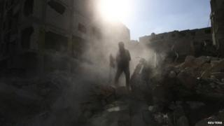 "A man looks for survivors amid the rubble of collapsed buildings after what activists said were eight air strikes by forces loyal to Syria""s President Bashar al-Assad in Douma Eastern Al-Ghouta, near Damascus 15 March 2015"