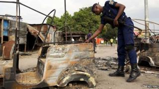 A policeman inspects damage outside a police station that was attacked during violent protests in Kinshasa, Democratic Republic of Congo on 23 January 2015