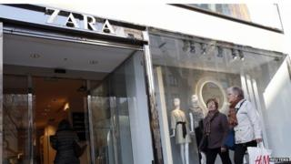 Women hold an H^M shopping bag outside a Zara store