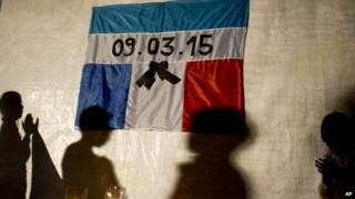 The shadows of children are cast on a tarp displaying the flags of Argentina and France and the date of the fatal helicopter crash during a silent march to honour the crash victims in Villa Castelli on 12 March 2015
