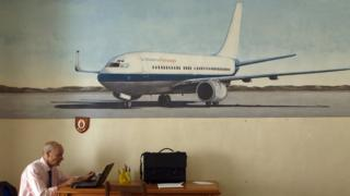 A man works in front of a mural of an aircraft of St Helena Airlines