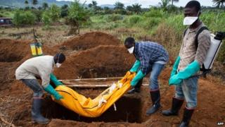 Volunteers in protective suit burry the body of a person who died from Ebola in Waterloo, some 30 kilometers southeast of Freetown, Sierra Leone, on October 7 2014