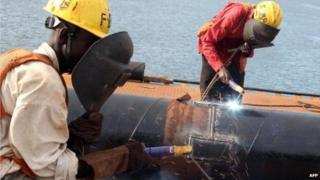Local Tanzanian welders work on the construction site of an ultra modern bridge by a Chinese company at Kurasini area in Dar es Salaam on 23 March 2013