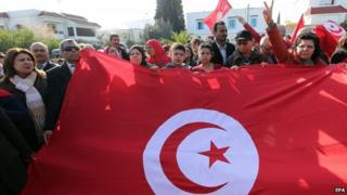 Tunisians wave their national flag as they protest outside the National Bardo Museum in Tunis, Tunisia on 19 March 2015