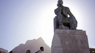 A student walks pass a statue of Cecil John Rhodes, University of Cape Town
