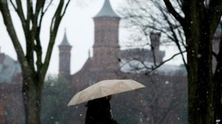 The Smithsonian Institution Building, known as The Castle is visible as a pedestrian makes their way through light snow along the National Mall on the first day of spring 20 March 2015