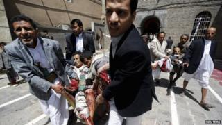 People carry the injured out of a mosque which was attacked by a suicide bomber in Sanaa, Yemen, 20 March 2015