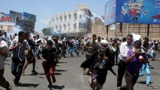 Protesters flee tear gas in Taiz in Yemen as the city was seized by Houthi rebels, 22 March 2015