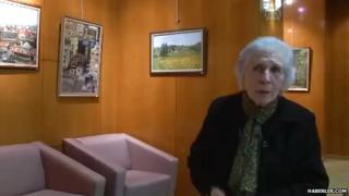 Fatma Mihriban Aktari in front of her paintings
