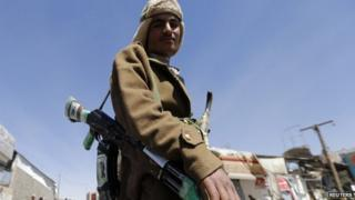 A Houthi fighter poses for a photo outside a presidential guards barrack on a mountain overlooking the presidential palace in Sanaa January 20, 2015