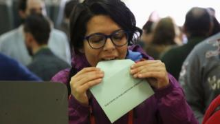 A woman prepares to cast her vote for the Andalusian regional elections at a polling station in the Andalusian capital of Seville