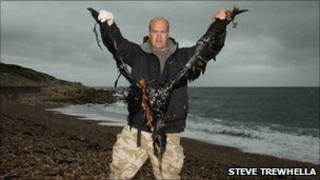 A man holding a dead gannet covered in oil PHOTO: Steve Trewhella