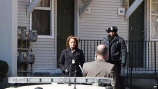 Police wait outside a home in Detroit where two children were found dead