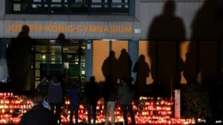 Students and wellwishers gather at a memorial of flowers and candles in front of Joseph Koenig school in Haltern am See. Photo: 25 March 2015