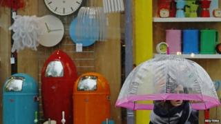 Woman passes household goods shop in Brighton