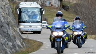 A bus transporting the families of the Germanwings Airbus A320 victims, escorted by French motorcycle policemen, arrive in Seyne-les-Alpes on March 26, 2015