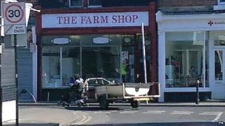 Person towing a boat behind an electric mobility scooter through Hartlepool