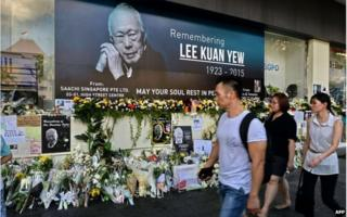 Pedestrians walk past a tribute corner for Singapore's late former prime minister Lee Kuan Yew who is lying in state at Parliament House in Singapore on 27 March 2015