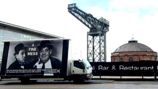 A poster on a van showing Ed Miliband and Alex Salmond as Laurel and Hardy, with the rotunda and Finnieston crane in the background