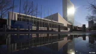 The United Nations building is reflected in a puddle in the Manhattan borough of New York
