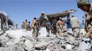 Soldiers and Houthi fighters inspect the damage caused by air strikes on the airport of Yemen's northwestern city of Saada on 30 March, 2015