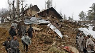 Police stand amidst the rubble after a hillside collapsed onto a house at Laden village, west of Srinagar, March 30, 2015