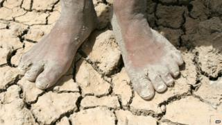 A boy stands on parched earth in a dry field on the outskirts of Najaf, Iraq