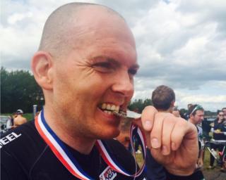 Craig biting a medal