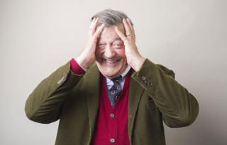 Stephen Fry with his head in his hands