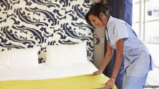 Hotel maid making a bed
