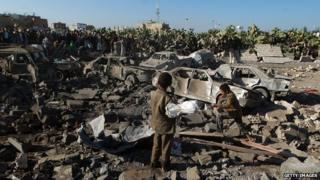 Yemenis stand at the site of a Saudi air strike against Huthi rebels near Sanaa Airport on March 26, 2015