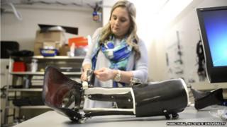 engineer adjusting exoskeleton boot