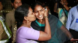 An Indian woman, left, greets her relative who arrived at Chhatrapati Shivaji International Airport in Mumbai, India, Thursday, April 2, 2015 after being evacuated from Yemen.