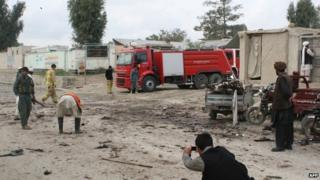 Afghan firefighters and others gather at the site of a suicide attack in Khost on April 2, 2015.
