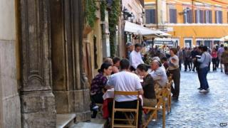 Diners eating outside a restaurant in Italy