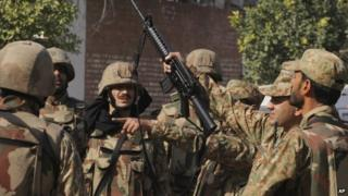 Pakistan army soldiers surround a Shia mosque attacked by suicide bombers and gunmen in Peshawar, Pakistan, Friday, Feb. 13, 2015.