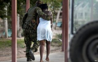 A woman is led away from the scene of an attack at Garissa University in April. A story about that massacre, which killed 147 people, went viral on social media after the Paris attacks on Friday