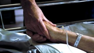 A nurse holds hand with an elderly patient in a hospital bed