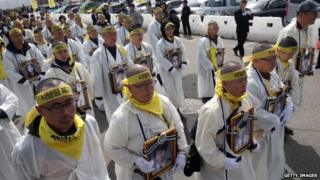 Grieving parents of victims of the Sewol ferry disaster, wearing white mourning robes with shaved heads