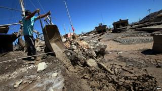 A man removes mud from his house after torrential rains and floods in Diego de Almagro, Chile, 28 March 2015.