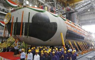 "Employees stand in front of the Indian Navy""s first Scorpene submarine before being undocked from Mazagon Docks Ltd, a naval vessel ship-building yard, in Mumbai April 6, 2015."