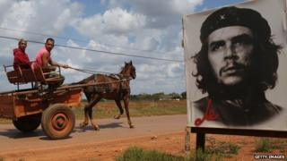 Two Cubans drive a horse and cart past a poster of Che Guevara