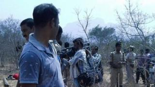 A security guard looks on as members of the media film the bodies of loggers killed by an anti-smuggling task force in a remote forest in the southern state of Andhra Pradesh on 7 April 2015.