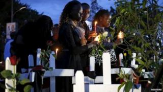 Kenyans hold candles next to wooden crosses symbolising the victims of an attack by gunmen at Garissa University College, during a memorial vigil at the Freedom Corner in Kenya's capital Nairobi o 7 April 2015