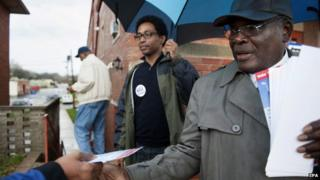 Ferguson City Council ward three candidates Lee Smith (R) and Wesley Bell (L) hand out election information during the municipal elections