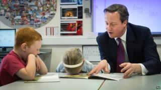 David Cameron helps with a reading lesson at the Sacred Heart Roman Catholic Primary School in Westhoughton near Bolton where he met pupils - 8 April 2015
