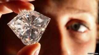 Man inspecting a large diamond