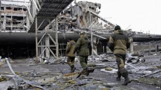 Pro-Russian separatists walk near the destroyed Donetsk International Airport, in Donetsk, Ukraine, 04 April 2015