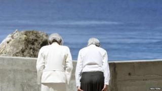 Japan's Emperor Akihito (R) and Empress Michiko bow towards Angaur Island after they offered flowers to the cenotaph for the war dead in the western Pacific area, on Palau's Peleliu Island, on 9 April 2015