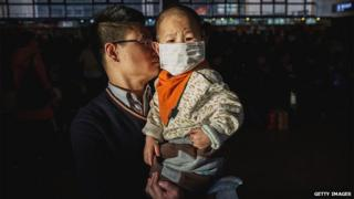 Chinese man holds his son, wearing a mask for pollution, as they wait in the departure area for a train at a local railway station on 16 February 2015 in Beijing, China.